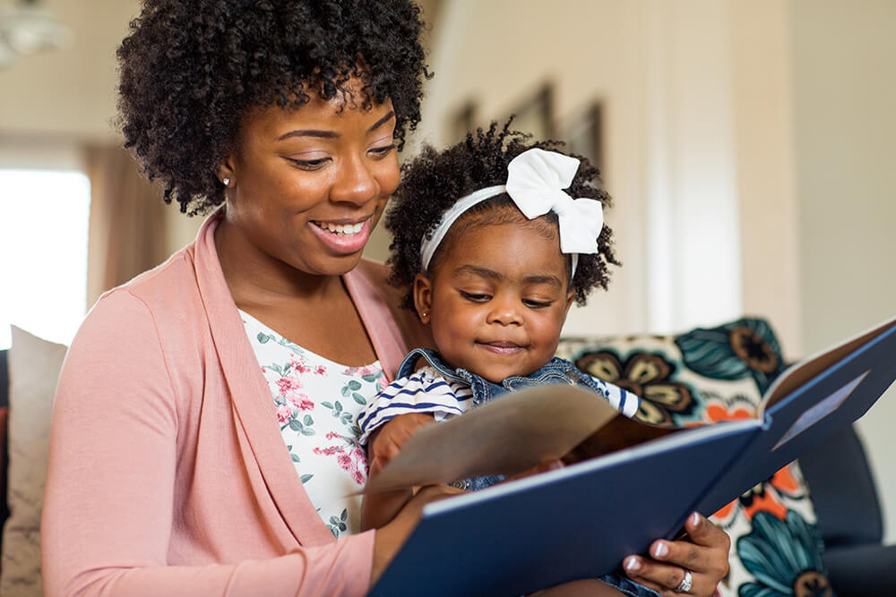 A daughter sits on her mother's lap at home while they read a book together