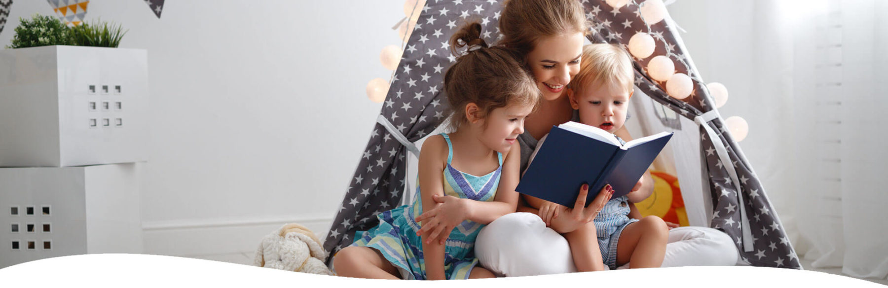 Mom reading to her young son and daughter in a bedroom fort